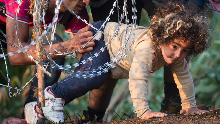 A refugee girl moves under barbed wire as she crosses from Serbia to Hungary, in Roszke, Thursday, Aug. 27, 2015. Over 10,000 migrants, including many women with babies and small children, have crossed into Serbia over the past few days and headed toward Hungary. (AP Photo/Darko Bandic)