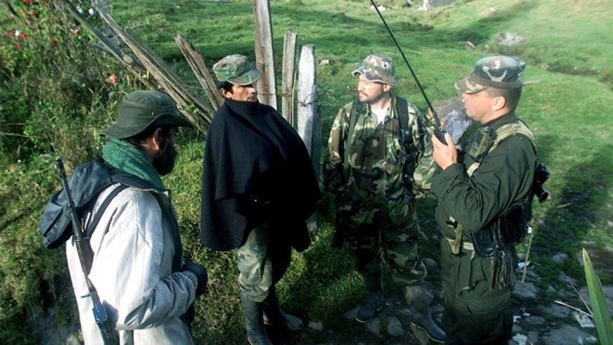 403499 01: (COLOMBIA OUT) Members of the Revolutionary Armed Forces of Colombia (FARC) listen to news from other FARC locations operating in the region April 7, 2002 in Cundinamarca, Colombia. The FARC guerrillas, once in San Vicente del Caguan, are now regrouping in the mountains of southern Bogota to allegedly start a new war strategy against the capital. (Photo by Carlos Villalon/Getty Images)