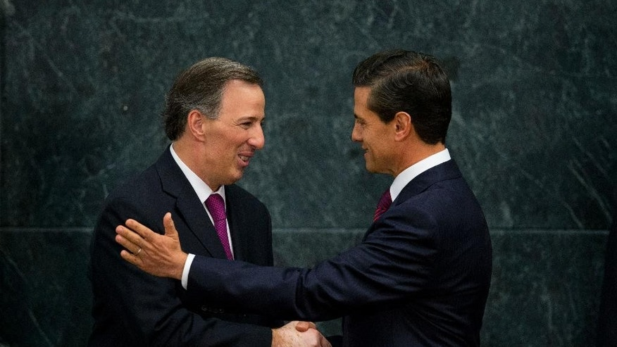 Mexico's President Enrique Pena Nieto, right, shakes hands with Jose Antonio Meade, former secretary of foreign relations and newly appointed secretary of social development, at a press conference to announce cabinet changes, at Los Pinos presidential residence, in Mexico City, Thursday, Aug. 27, 2015. The president, facing declining popularity, announced major changes to his cabinet, including a new secretary of foreign relations and a new national security commissioner.(AP Photo/Rebecca Blackwell)