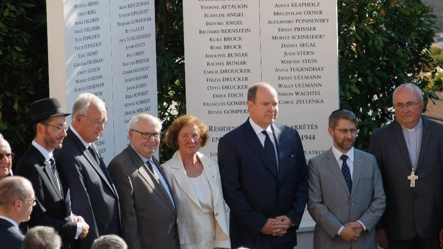 Prince Albert II, 3rd right, stands with French Nazi hunter Serge Klarsfeld, 3rd left, and his wife Beate, centre, after unveiling a monument to Jews deported from the Riviera principality during World War II, as part of a larger effort to shed light at last on a troubling chapter in the country's history, in a cemetery in Monaco, Thursday, Aug. 27, 2015. Prince Albert II presented the monument Thursday, marking 73 years since Monegasque authorities under Nazi occupation rounded up several Jews on the night of Aug. 27-28, 1942. (AP Photo/Claude Paris)