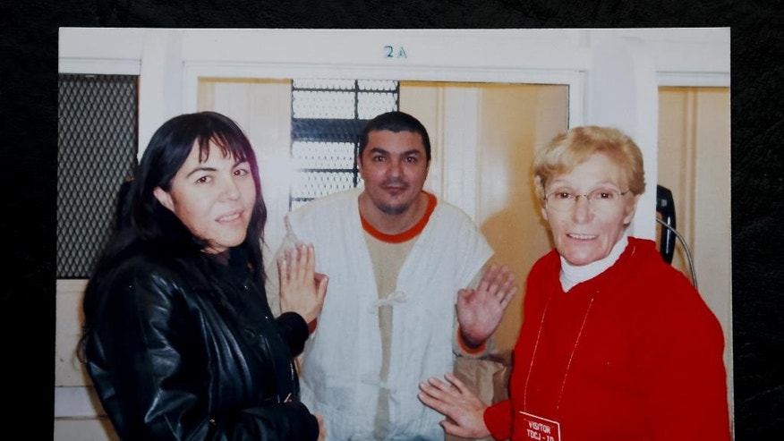 In this undated photo courtesy of Lidia Guerrero, she and her daughter Ada Saldano pose with her son Victor while he's on death row at the Polunsky Unit of the Texas Department of Criminal Justice, near Houston, Texas. There's no doubt that Saldano pulled the trigger that killed Paul King in Dallas in 1995, but there has been a legal row over whether he should have received the death penalty. (Lidia Guerrero via AP)