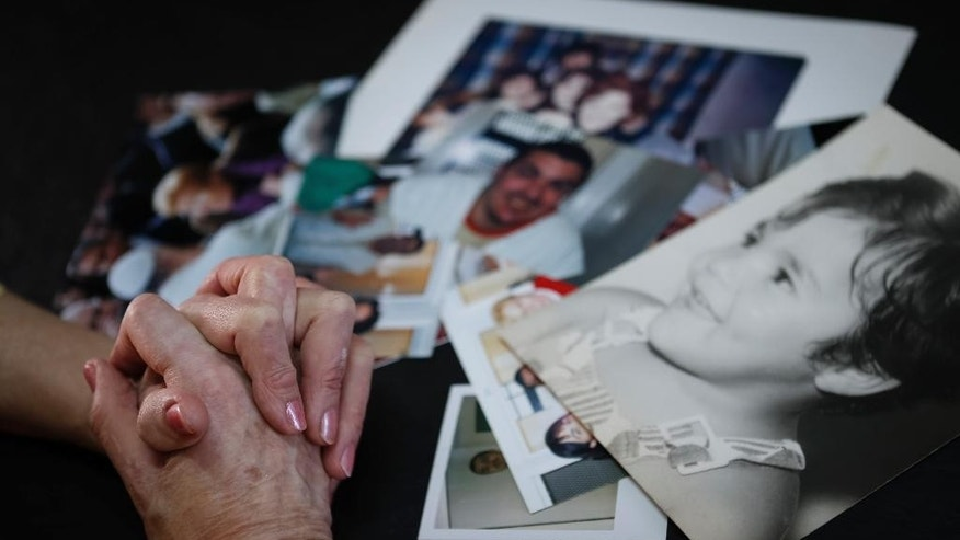 In this Aug. 22, 2015 photo, Lidia Guerrero crosses her hands over photographs of her son Victor Saldano, a convicted murderer who has been on death row in Texas for 19 years, inside her home in Cordoba, Argentina. Death penalty opponents are hoping that Pope Francis pressures U.S. lawmakers to abolish the practice when he visits the United States next month, and Guerrero is praying that the pope intervenes on behalf of her son. (AP Photo/Nico Aguilera)