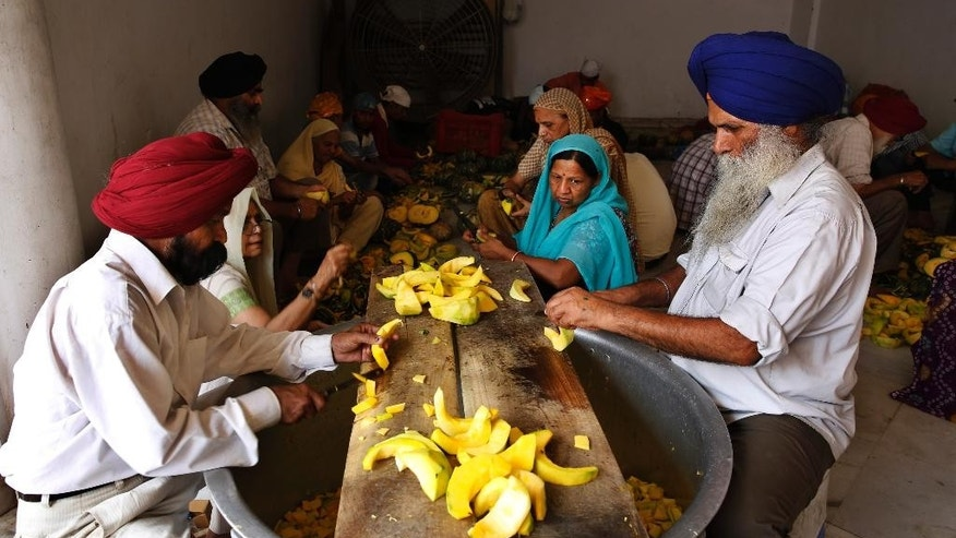 In this May 19, 2015 photo, volunteers and devotees cut vegetables as the prepare langar, which translates to community dinner, at Bangla Sahib Gurudwara or Sikh temple, in New Delhi, India. Service is one of the most integral traditions of gurudwaras. From cleaning to preparing tons of food every day there is plenty of work to be done. And there are plenty of sevadaars, or volunteers, to do it. Men, women and children throng the kitchen at Bangla Sahib, one of the biggest gurudwara in India that feeds more than 10,000 people every day. (AP Photo/Manish Swarup)