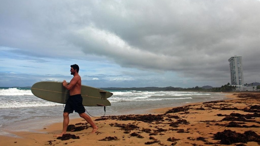 A surfer walks into the ocean as Tropical Storm Erika approaches the island in Luquillo, Puerto Rico, Thursday, Aug. 27, 2015. Tropical Storm Erika pummeled the eastern Caribbean island of Dominica, unleashing landslides and killing at least four people. The storm knocked out power and water supplies and had dumped 15 inches of rain on Dominica by early Thursday, according to the weather service in the nearby island of Antigua. (AP Photo/Ricardo Arduengo)