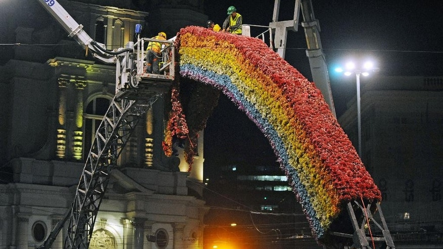 "Workers dismantle the controversial art installation ""The Rainbow,"" burnt several times by right wing extremists, seeing in it a symbol of gay movement and later reconstructed, at the Savior Square in Warsaw, Poland, Thursday, Aug. 27, 2015. The installation was put down because the location was temporary and the agreement between the owner and city authorities expired. (AP Photo/Alik Keplicz)"