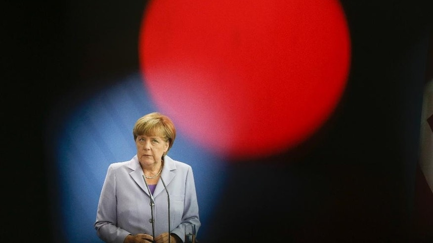 In this photo taken with a control light on a television camera in front German Chancellor Angela Merkel attends a news conference with Danish Prime Minister Lars Loekke Rasmussen after talks at the chancellery in Berlin, Friday, Aug. 28, 2015. (AP Photo/Markus Schreiber).
