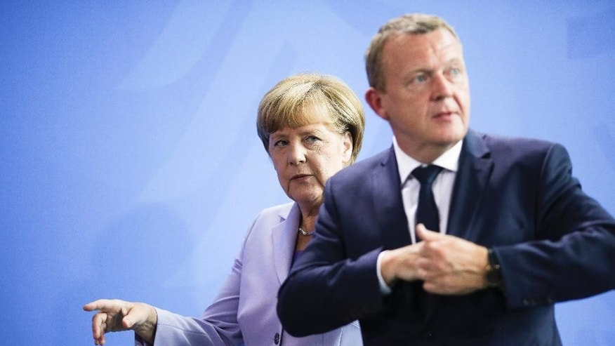 German Chancellor Angela Merkel, left, and Danish Prime Minister Lars Loekke Rasmussen leave a news conference after talks at the chancellery in Berlin, Friday, Aug. 28, 2015. (AP Photo/Markus Schreiber).