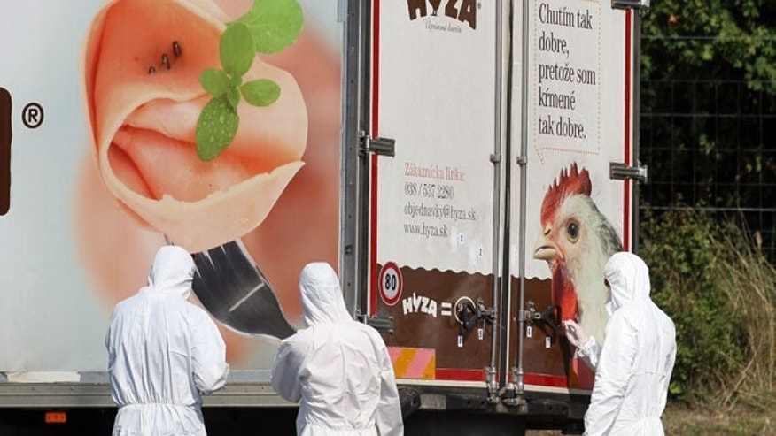 Aug. 27, 2015: Investigators stand near a truck on the shoulder of the highway A4 near Parndorf south of Vienna, Austria. (AP Photo/Ronald Zak)