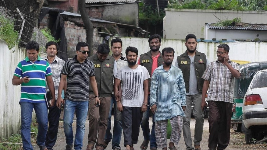 Suspected Muslim militants Kausar Hossain Khan, 29, foreground third right, and Kamal Hossain Sardar, 29, foreground center, who were arrested in the killing of a secular blogger, are escorted to appear before the media in Dhaka, Bangladesh, Friday, Aug. 28, 2015. Police in Bangladesh have arrested two more suspected members of a banned militant group thought to be behind the slaying of a secular blogger in the fourth such deadly attack this year. (AP Photo/A.M. Ahad)