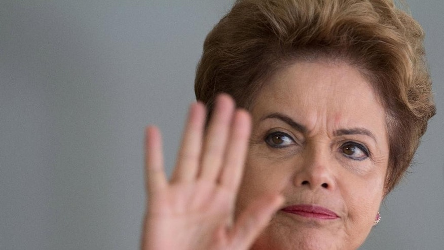 FILE - In this July 17, 2015 file photo, Brazil's President Dilma Rousseff waves to the press as she arrives to greet leaders arriving for a Mercosur Summit at Itamaraty Palace in Brasilia, Brazil. Dep. Eduardo Cunha, the speaker of Brazil's lower house of Congress is Rousseff's sworn enemy who has been charged with taking millions in bribes in connection to a sprawling corruption scandal at state-run oil company Petrobras. He's also the man who can call for an impeachment vote in the House of Deputies against the president, an action that two-thirds of Brazilians polled say they want to see happen. (AP Photo/Joedson Alves, File)