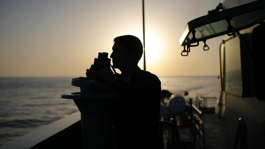 In this photo taken on Wednesday, Aug. 26, 2015, a Portuguese navy ship NPR Viana do Castelo's crew member uses binoculars during a European Frontex migrant search and rescue mission in the Mediterranean Sea, off the southeastern coast of Spain. During the operation the ship searched for the bodies of a suspected migrant boat that sank few days earlier, following a report by Spanish police. (AP Photo/Francisco Seco)