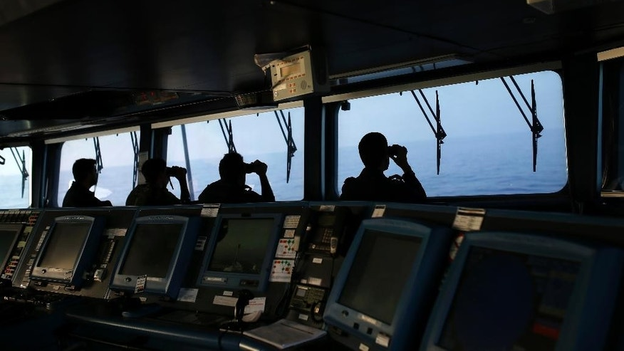 In this photo taken on Wednesday, Aug. 26, 2015, Portuguese navy ship NPR Viana do Castelo's crew members use binoculars on the bridge during a European Frontex migrant search and rescue mission in the Mediterranean Sea, off the southeastern coast of Spain. During the operation the ship searched for the bodies of a suspected migrant boat that sank few days earlier, following a report by Spanish police. (AP Photo/Francisco Seco)