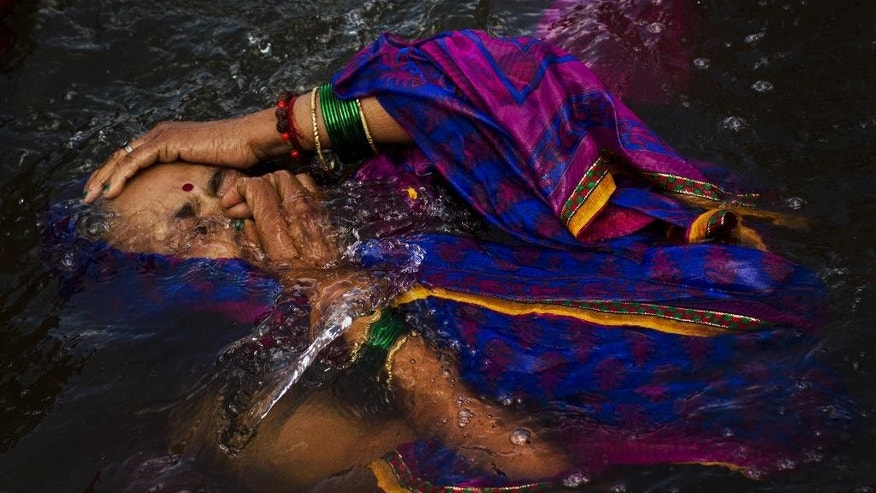 In this Wednesday, Aug. 26, 2015, photo, a Hindu devotee performs a holy dip in the Godavari River during Kumbh Mela, or Pitcher Festival, in Nasik, India. Water is central to many religions: Christians perform baptisms, Orthodox Jews seek ritual purity in mikvah baths, Muslims wash themselves before prayer. To the millions of Hindus expected at the Kumbh Mela festival, held this year along the Godavari, touching that water, which is far from the cleanest you could find, is reverential. (AP Photo/Bernat Armangue)