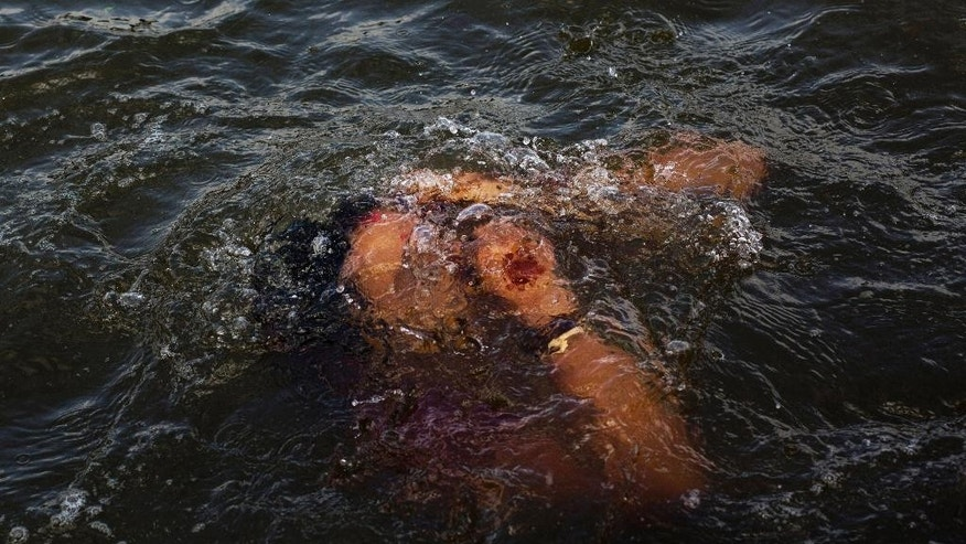 In this Wednesday, Aug. 26, 2015, photo, a Hindu devotee performs a holy dip in the Godavari River during Kumbh Mela, or Pitcher Festival, in Nasik, India. It's just water, and far from the cleanest you could find. Raw sewage often flows in the Godavari River, bringing with it high bacteria levels. Residue from sand mining can cloud the water. Farm pesticides leech through the soil. But to the millions of Hindus expected at the Kumbh Mela festival, held this year along the Godavari, touching that water is reverential. (AP Photo/Bernat Armangue)