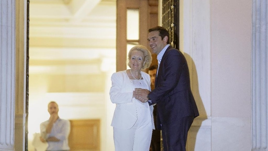 Outgoing Prime Minister Alexis Tsipras, right, shakes hands with Greece's new Prime Minister Vassiliki Thanou, after a handover ceremony as he leaves the Maximou mansion in Athens, on Thursday, Aug. 27, 2015. Greece came one step closer on Thursday to early elections with President Prokopis Pavlopoulos appointing the head of the country's Supreme Court Vassiliki Thanou as caretaker prime minister to lead the country to next month's polls.(AP Photo/Petros Giannakouris)