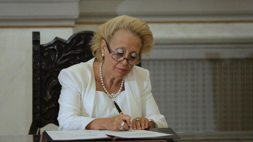 Vassiliki Thanou, signs a document during a swearing in ceremony at the Presidential Palace in Athens, Thursday, Aug. 27, 2015, to become Greece's first female prime minister. Greece came one step closer on Thursday to early elections with President Prokopis Pavlopoulos appointing the head of the country's Supreme Court as caretaker prime minister to lead the country to next month's polls.(AP Photo/Petros Giannakouris)