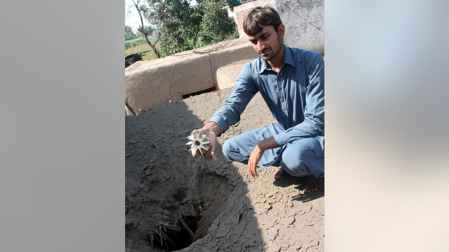 A Pakistani villager shows a remain of a morter landed at his house in border town of Kanganpur near Sialkot, Pakistan, Friday, Aug. 28, 2015.  Indian and Pakistani border guards traded gunfire in the divided region of Kashmir, leaving many civilians dead and another wounded, authorities said Friday. (AP Photo/Shahid Ikram)