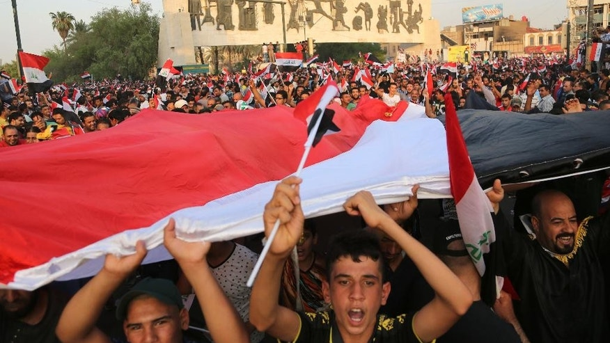 Protesters chant slogans in support of Iraqi Prime Minister Haider al-Abadi as they carry a large national flag during a rally in Tahrir Square in Baghdad, Iraq, Friday, Aug. 28, 2015. Friday's protesters were joined for the first time by followers of Muqtada al-Sadr, a radical, anti-American Shiite cleric. The protesters have staged weekly rallies since last month to press demands for reforms, better services and an end to corruption. (AP Photo/Karim Kadim)