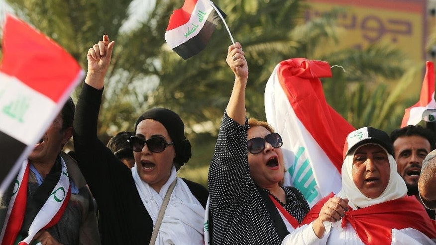 Protesters chant in support of Iraqi Prime Minister Haider al-Abadi as they carry national flags during a demonstration in Tahrir Square in Baghdad, Iraq, Friday, Aug. 28, 2015. Friday's protesters were joined for the first time by followers of Muqtada al-Sadr, a radical, anti-American Shiite cleric. The protesters have staged weekly rallies since last month to press demands for reforms, better services and an end to corruption. (AP Photo/Karim Kadim)