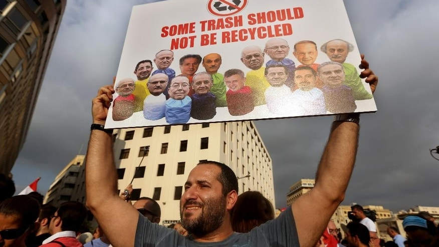 FILE -- In this August 22, file photo, a Lebanese activist holds a poster with pictures of Lebanese Cabinet ministers during a protest against the ongoing trash crisis, in downtown Beirut, Lebanon. To the casual visitor, Lebanon may look like a relative success story: a tiny slice of modernity and coexistence in a turbulent region plagued by violence and extremism _ but the reality is quite different. For residents, it's a failed state  eaten away by a sectarian political class, and while recent trash protests have challenged that system, others argue it's what's allowed a country of 4.5 million people from 18 recognized sects to survive. (AP Photo/Bilal Hussein, File)