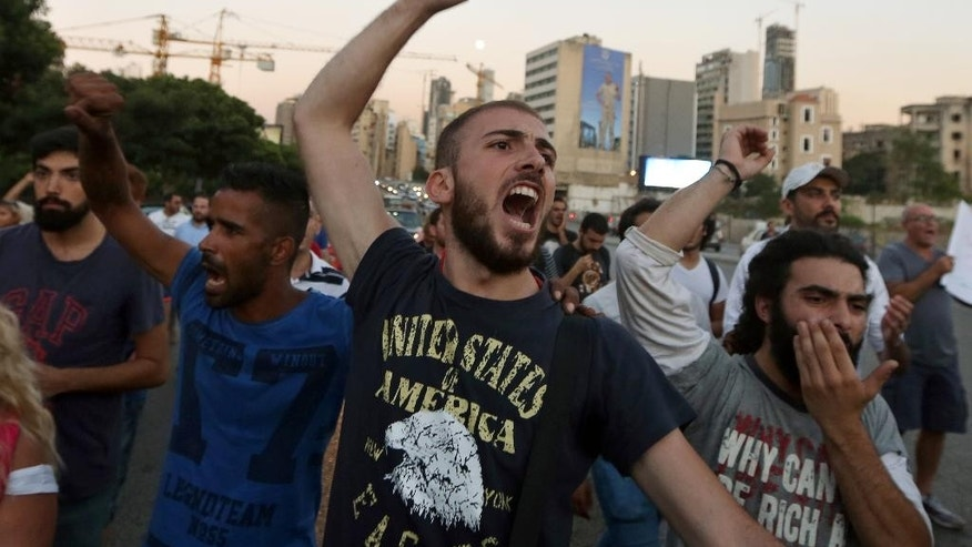 Lebanese activists chant slogans during a march against the trash crisis and government corruption in Beirut streets, Lebanon, Friday, Aug. 28, 2015. To the casual visitor, Lebanon may look like a relative success story: a tiny slice of modernity and coexistence in a turbulent region plagued by violence and extremism _ but the reality is quite different.  (AP Photo/Bilal Hussein)