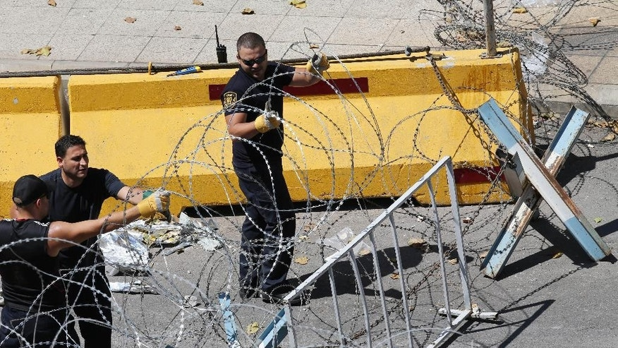 U.N. security officers, set up more barbed wire barriers in an extra security measure around the United Nations headquarters, which is in front the Lebanese government building, where the anti-government protesters hold their daily demonstrations, in downtown Beirut, Lebanon, Friday, Aug. 28, 2015. Beirut has been jolted by daily protests for the past week, including two massive demonstrations that turned violent over the weekend. (AP Photo/Hussein Malla)