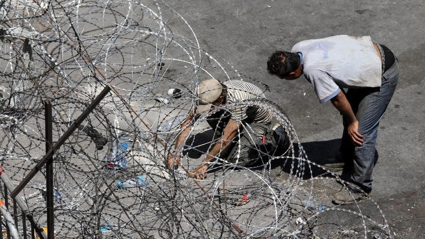 Lebanese workers who work for the police, set up more barbed wire barriers as an extra security measure around the Lebanese government building where the anti-government protesters hold their daily demonstrations, in downtown Beirut, Lebanon, Friday, Aug. 28, 2015. Beirut has been jolted by daily protests for the past week, including two massive demonstrations that turned violent over the weekend. (AP Photo/Hussein Malla)