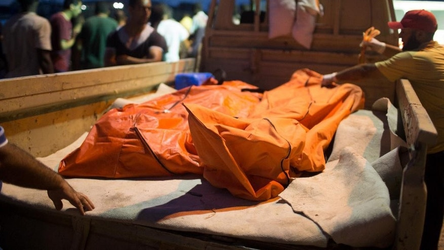 In this Thursday, Aug. 27, 2015 photo, bodies of migrants are taken from the scene of a capsized boat in Zuwara, Libya. (AP Photo/Mohamed Ben Khalifa)