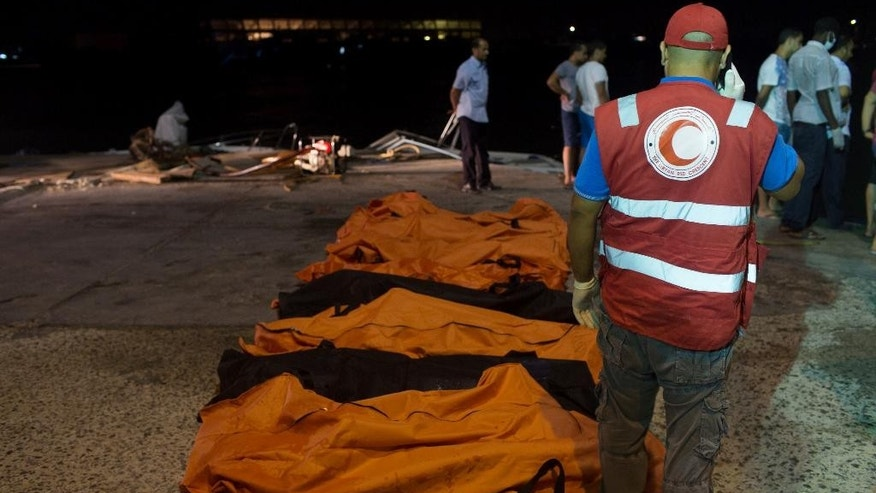 In this Thursday, Aug. 27, 2015 photo, rescuers gather around the bodies of drowned migrants in Zuwara, Libya. (AP Photo/Mohamed Ben Khalifa)