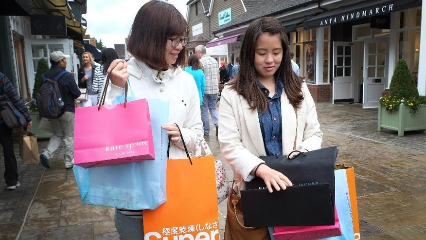 FOR STORY BY SYLVIA HUI - BRITAIN LUXURY GOODS CHINA - Shoppers carry designer label branded bags at Bicester Village designer outlet centre, in Bicester, England, in this photo dated Wednesday, Aug. 26, 2015. Chinese customers have become a powerful market force in the global trade in expensive clothes, jewelry, watches, perfumes and handbags, but nobody knows how the recent turmoil in Chinese financial markets will impact on the sales of designer brands. (AP Photo/Kirsty Wigglesworth)