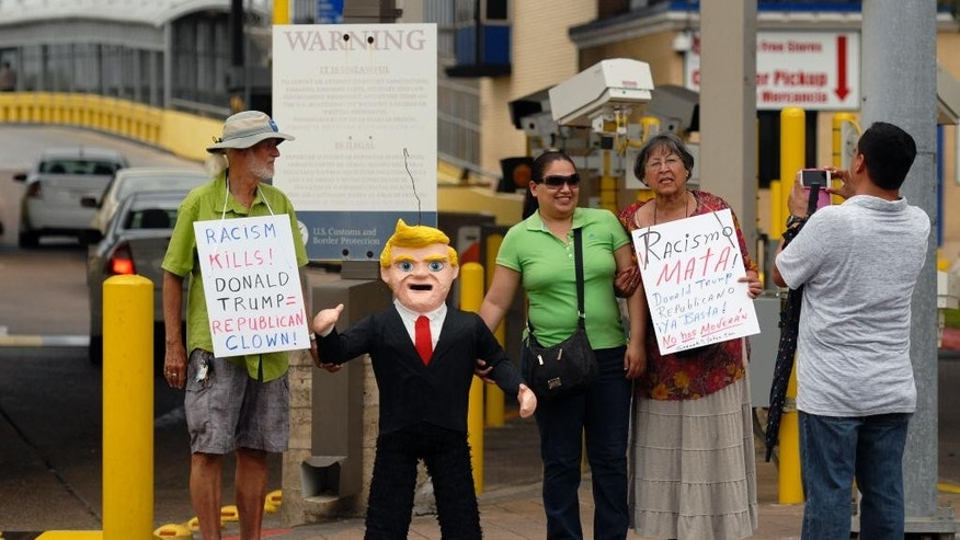 FILE - In this July 31, 2015 file photo, two women pose for a photo standing next to a pinata in the likeness of Donald Trump, during a protest against Trump and derogatory remarks he has made about Mexicans, in Brownsville, Texas. Mexico's ambassador-designate to Washington, Miguel Basanez, sought to downplay Trump's comments on Mexico, telling a Senate confirmation hearing on Friday, Aug. 28, 2015, that Trump is simply playing politics. (Brad Doherty/The Brownsville Herald via AP) MANDATORY CREDIT