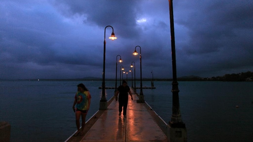 A couple walks on a pier under cloudy skies as Tropical Storm Erika approaches the island in Naguabo, Puerto Rico, Thursday, Aug. 27, 2015. Erika was expected to move near Puerto Rico and the Virgin Islands on Thursday and be near or just north of the Dominican Republic on Friday as it heads toward Florida early next week, possibly as a hurricane. (AP Photo/Ricardo Arduengo)