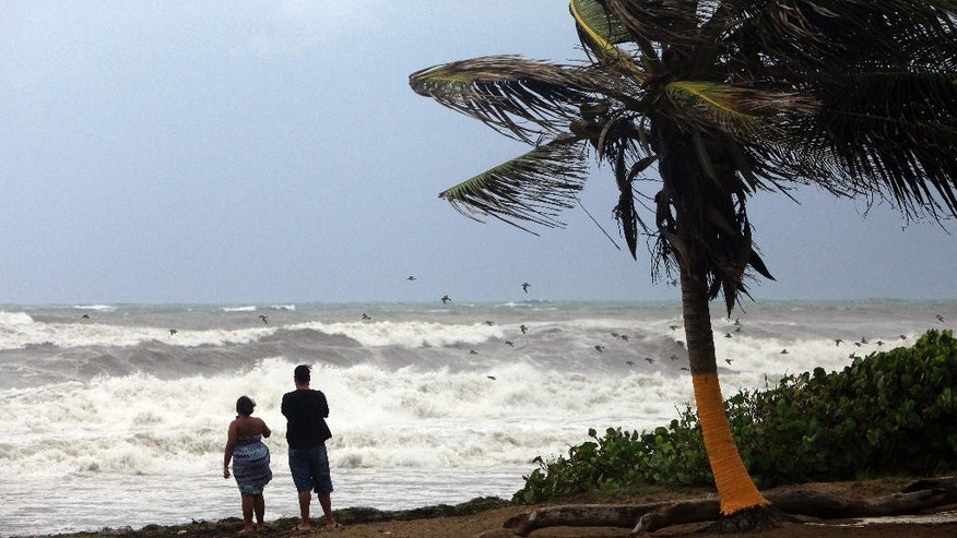 A couple looks out at a rough sea as Tropical Storm Erika moves away from the area in Guayama, Puerto Rico, Friday, Aug. 28, 2015. The storm was expected to dump up to 8 inches of rain across the drought-stricken northern Caribbean as it carved a path toward the U.S. (AP Photo/Ricardo Arduengo)