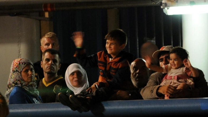 Migrants wait to disembark from Swedish ship Poseidon at the Palermo harbor, Italy, Thursday, Aug. 27, 2015. The Poseidon rescued 569 people off the Libyan coast in two different operations, finding 51 more dead migrants in the skull of on of the boats. The U.N. refugee agency says more than 2,400 people have died at sea so far this year making the crossing. More than 110,000 migrants have been rescued and brought to southern Italian ports. (AP Photo/Alessandro Fucarini)
