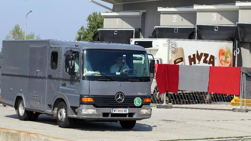 Blankets cover the view on a truck that is investigated at a veterinary border station as a hearse passes by at the Austrian/Hungarian border in Nickelsdorf, Austria, Friday, Aug 28, 2015. The truck was found parked on a main Austrian highway on Thursday with 71 migrants suffocated to death. (AP Photo/Ronald Zak)