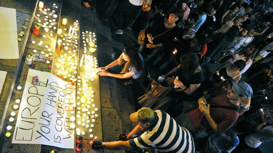 """People light candles by a sign that reads """"Europe: your hand is covered with blood"""" at Keleti railway station in Budapest, Hungary, Friday, Aug. 28, 2015, during a memorial for the 71 migrants who suffocated to death on the previous day in an abandoned truck on a main Austrian highway. (Tamas Kovacs/MTI via AP)"""
