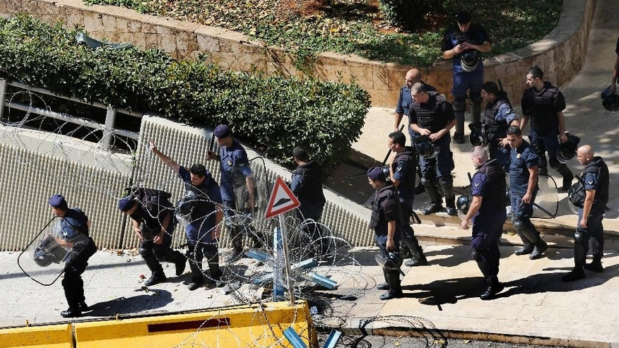 Lebanese riot policemen pass under barbed wire barriers, as they start deploying around the government building where anti-government protesters hold their daily demonstrations, in downtown Beirut, Lebanon, Saturday, Aug. 29, 2015. The London-based rights group Amnesty is calling on Lebanese authorities to investigate allegations that security forces have used excessive force to disperse rallies protesting the government failure to deal with garbage pilling in the streets. The statement comes ahead of a major rally planned in Beirut Saturday amid worries it would also descend into clashes. (AP Photo/Hussein Malla)