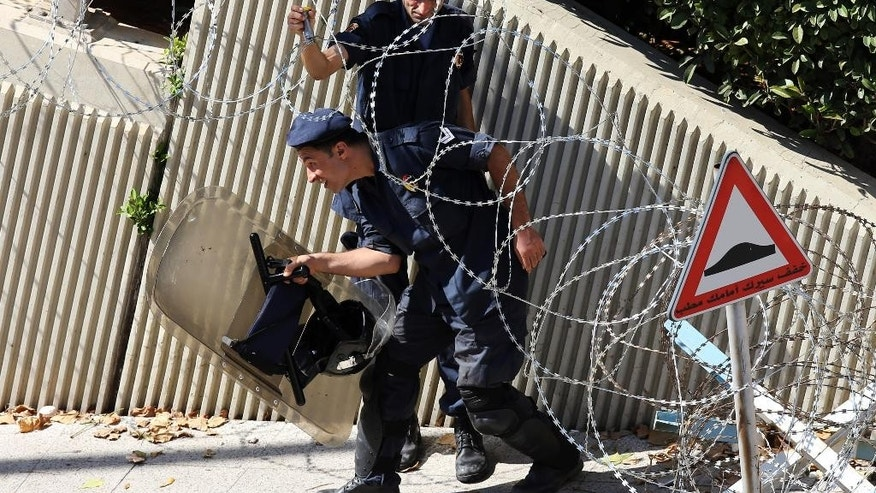 A Lebanese riot policeman, background, holds up a barbed wire barrier to help his colleague pass under it, as they start deploying around the government building where anti-government protesters hold their daily demonstrations, in downtown Beirut, Lebanon, Saturday, Aug. 29, 2015. The London-based rights group Amnesty is calling on Lebanese authorities to investigate allegations that security forces have used excessive force to disperse rallies protesting the government failure to deal with garbage piling up in the streets. The statement comes ahead of a major rally planned in Beirut Saturday amid worries it would also descend into clashes. (AP Photo/Hussein Malla)
