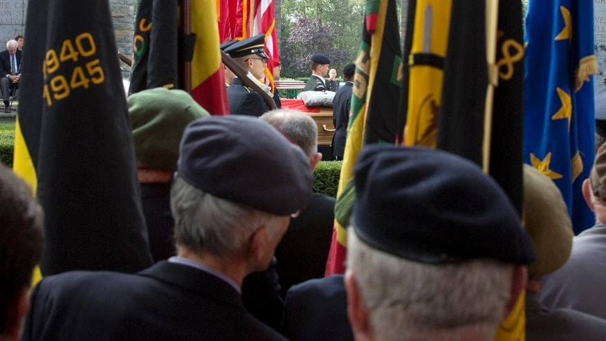 Belgian veterans catch a glimpse of the coffin of Belgian nurse Augusta Chiwy between flags during a memorial service at the Mardasson Memorial in Bastogne, Belgium on Saturday, Aug. 29, 2015. Augusta Chiwy, 94, a Belgian nurse who helped save hundreds of American soldiers during the Battle of the Bulge at the end of World War II, was buried Saturday near where thousands of Allied troops fell. (AP Photo/Virginia Mayo)