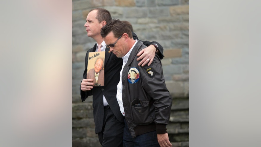 Belgian soldier Eric Lemoine, left, puts his arm on a friends shoulder as he leaves after a memorial service for Belgian nurse Augusta Chiwy at the Mardasson Memorial in Bastogne, Belgium on Saturday, Aug. 29, 2015. Augusta Chiwy, 94, a Belgian nurse who helped save hundreds of American soldiers during the Battle of the Bulge at the end of World War II, was buried Saturday near where thousands of Allied troops fell. (AP Photo/Virginia Mayo)