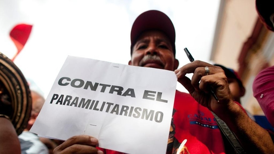 "A man holds a sign that reads in Spanish ""Against paramilitarism,"" referring to Colombian paramilitary groups, during a rally to support the closing of the Colombian border, in Caracas, Venezuela, Friday, Aug. 28, 2015. Venezuelan President Nicolas Maduro announced that he would extend the week-old partial closure of the border with Colombia to more cities and send additional troops to the area, doubling down on a policy has drawn rebuke by Colombian leaders. (AP Photo/Ariana Cubillos)"