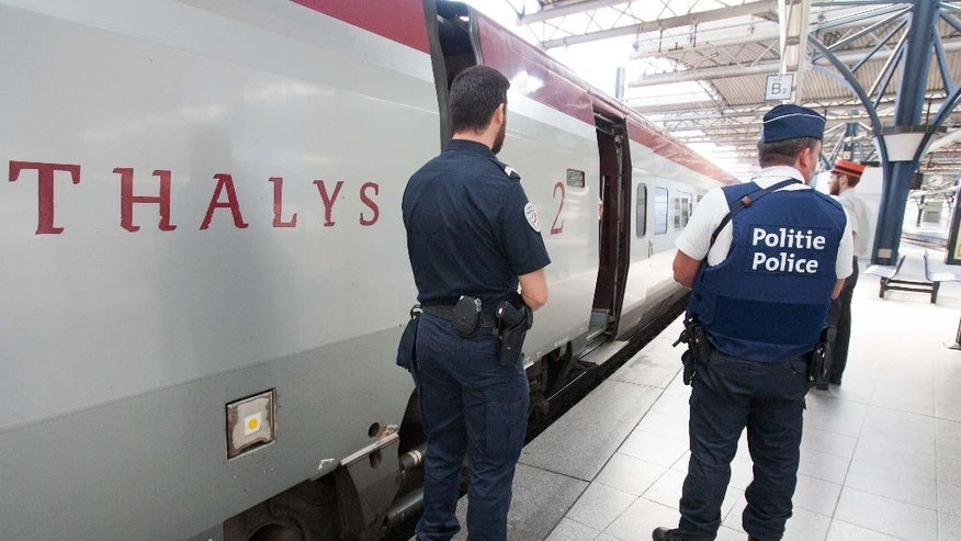 FILE - In this Aug.22, 2015 file photo, member of Belgian and French police stay next to a Thalys train at the Brussels Midi - Zuid train station. The attack Aug. 21 on the Thalys train from Amsterdam to Paris happened at the height of the summer travel season. France hosts emergency talks in Paris on Saturday, with representatives from other high-speed international rail nations, Belgium, Britain, Germany, Italy, Luxembourg, the Netherlands, Spain and Switzerland. (AP Photo/Francois Walschaerts, File)