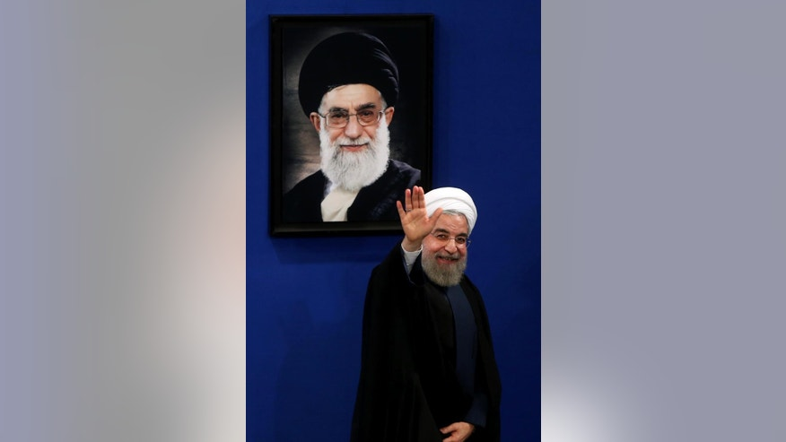 Iran's President Hassan Rouhani waves to reporters at the conclusion of his press conference in Tehran, Iran, Saturday, Aug. 29, 2015. Rouhani said Saturday he opposed a parliamentary vote on the landmark nuclear deal reached with world powers, saying terms of the agreement will turn into legal obligation if it is passed by the house. A picture of Supreme Leader Ayatollah Ali Khamenei hangs on the wall. (AP Photo/Ebrahim Noroozi)