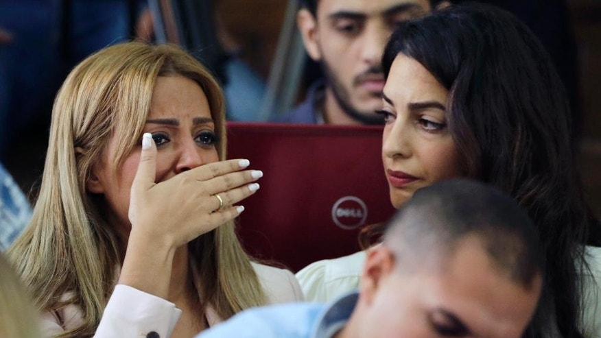 Marwa Fahmy wife of Canadian Al-Jazeera English journalist Mohammed Fahmy, bursts into tears, as she is watched by human rights lawyer Amal Clooney, after the verdict in a courtroom in Tora prison in Cairo, Egypt, Saturday, Aug. 29, 2015. An Egyptian court on Saturday sentenced three Al-Jazeera English journalists to three years in prison, the last twist in a long-running trial criticized worldwide by press freedom advocates and human rights activists. (AP Photo/Amr Nabil)