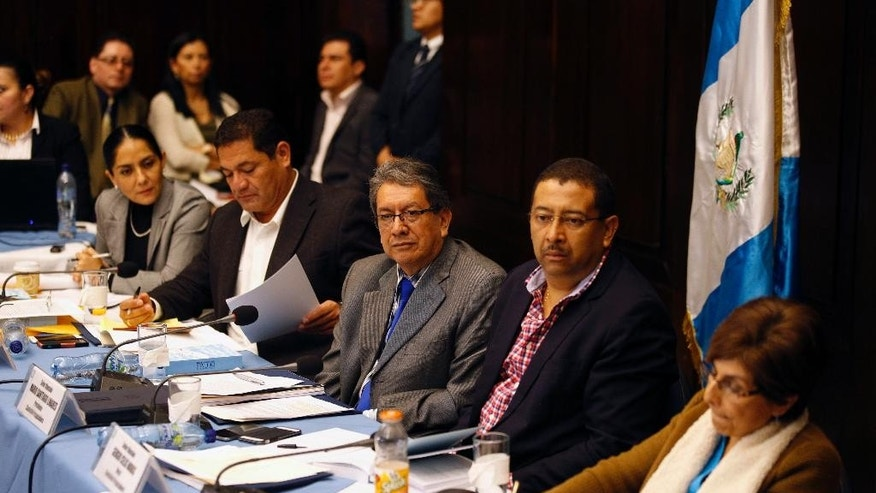 Members of the commission that will decide whether to remove Guatemalan President Otto Perez Molina's immunity listen to special prosecutors from the Attorney General's office, in Guatemala City, Friday, Aug. 28, 2015. The commission has decided call Perez Molina to appear before the body as a corruption scandal swirls around his government. (AP Photo/Luis Soto)
