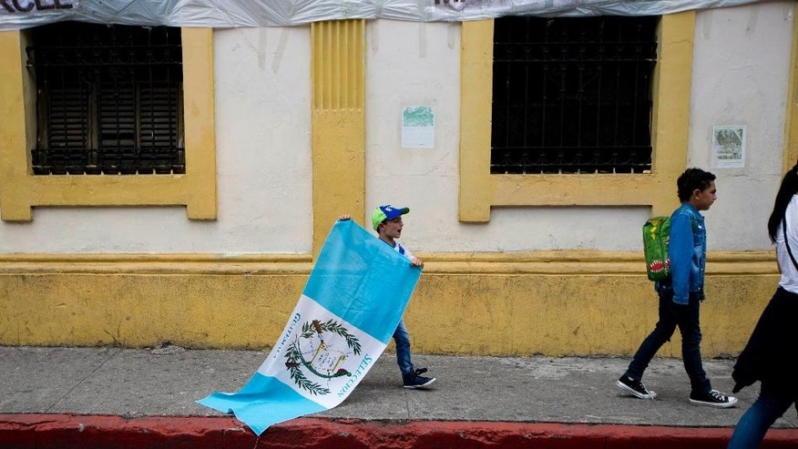Holding a Guatemalan national flag, a boy walks with his family to join a protest demanding the resignation of Guatemala's President Otto Perez Molina outside the Congress building, in Guatemala City, Saturday, Aug. 29, 2015. Perez Molina failed to appear before a congressional commission investigating whether to lift his immunity from prosecution in a corruption case involving his government. The Guatemalan leader opted to send his personal attorney Saturday with a written declaration. (AP Photo/Moises Castillo)