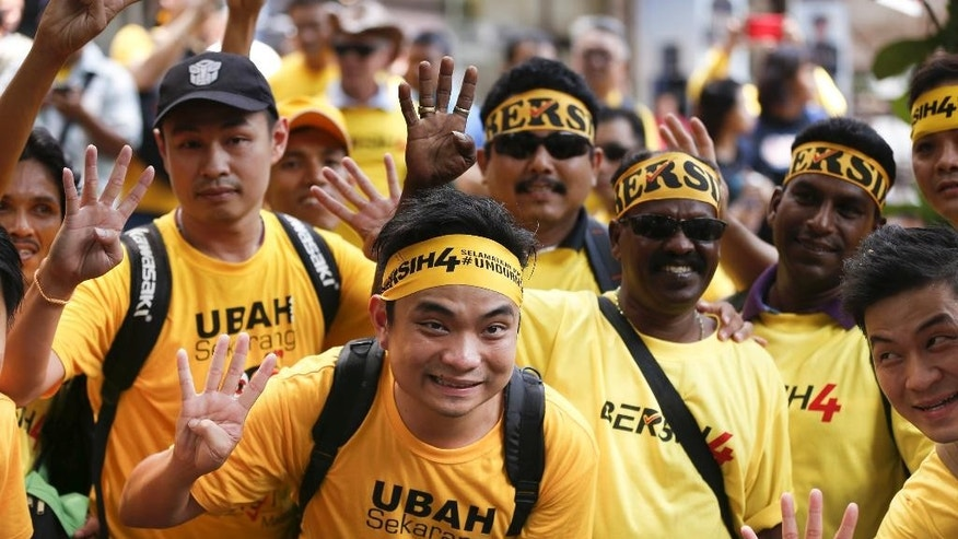 """Supporters of pro-democracy group """"Bersih"""" (Clean) pose for photographer before the start of a rally in Kuala Lumpur, Malaysia, Saturday, Aug. 29, 2015. Malaysian activists are putting more pressure on embattled Prime Minister Najib Razak to resign with major street rallies this weekend following allegations of suspicious money transfers into his accounts. (AP Photo/Lai Seng Sin)"""