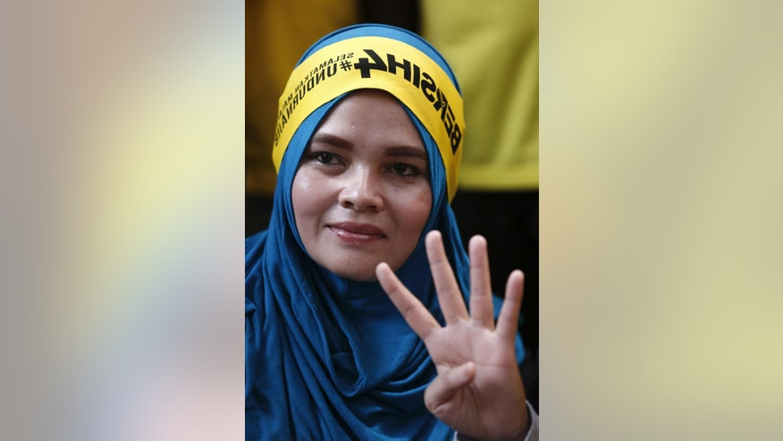 """A woman participant shows the support for the rally of pro-democracy group """"Bersih"""" (Clean) in Kuala Lumpur, Malaysia, Saturday, Aug. 29, 2015. Malaysian activists are putting more pressure on embattled Prime Minister Najib Razak to resign with major street rallies this weekend following allegations of suspicious money transfers into his accounts. (AP Photo/Lai Seng Sin)"""
