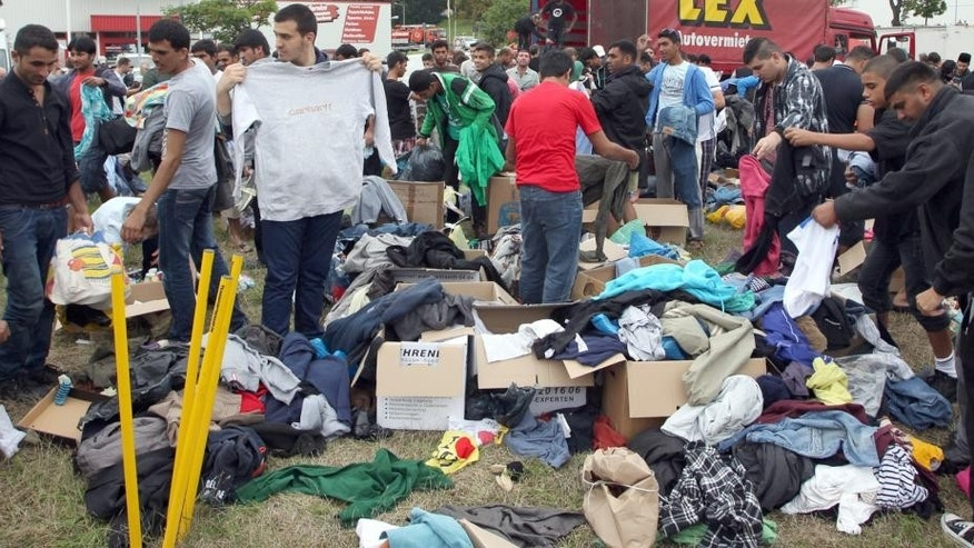 In this Aug. 28, 2015 picture refugees look for fitting clothes among the donated items at a welcome party for refugees in Heideau, Germany. Local authorities had imposed a blanket ban on public assemblies to prevent a repeat of the violence that occurred outside a refugee shelter last weekend, in which dozens of police officers were injured. The ban was partially lifted by a court to allow a welcome party for refugees to take place. (Sebastian Willnow/dpa via AP)