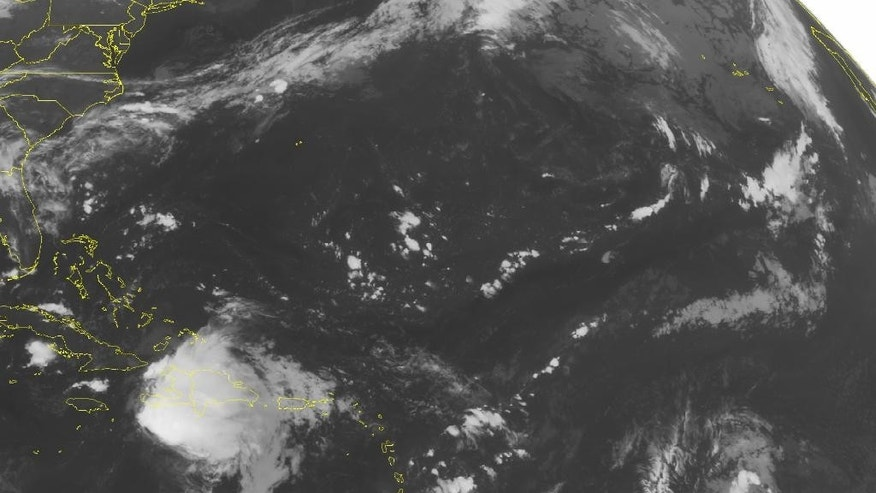 This NOAA satellite image taken Saturday, Aug. 29, 2015, at 12:45 a.m. EDT shows Tropical Storm Erika over Hispaniola producing heavy amounts of rain, embedded thunderstorms with weakening winds. Erika is moving towards Cuba but is expected to weaken. A weak disturbance across the Bahamas and Cuba is also producing scattered thunderstorms. (Weather Underground via AP)